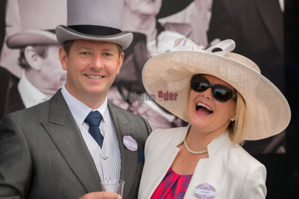 A man in grey morning dress with a top hat, blue tie and matching handkerchief and wearing a badge for the Royal Enclosure at Ascot is standing next to his wife, who is wearing a colourful dress under a cream jacket with a pearl necklace and earrings, sunglasses and a cream mesh hat. They have their arms round each other and are both laughing and smiling at the camera. In the background is a poster on the wall showing men in top hats and morning dress.